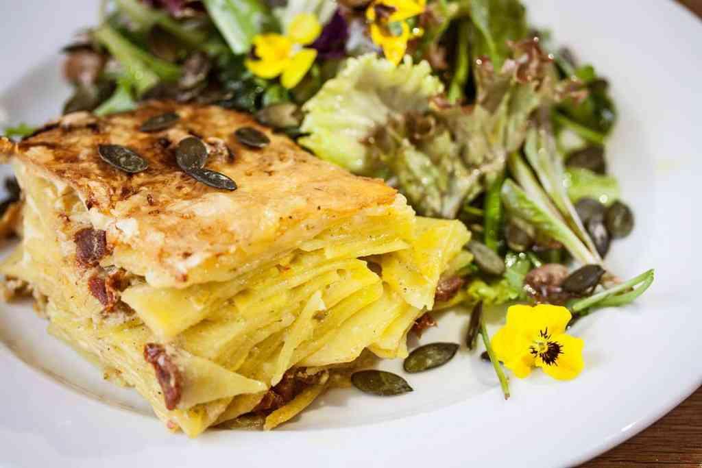 So lecker ist Clean Eating: Wildkräutersalat mit cremigem Pesto-Rosso Kartoffelauflauf. Das Rezept dazu finden Sie hier